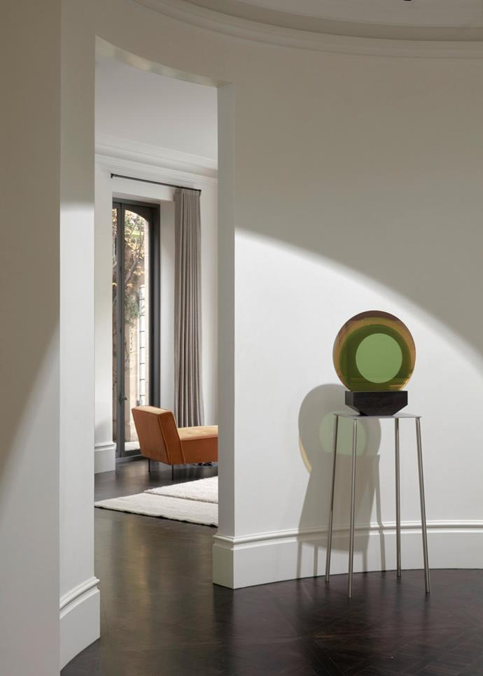 View from the central circular foyer into one of the rear living spaces. Sculptural artwork by Consuelo Cavaniglia from STATION gallery. The home's old parquetry floors were stained black but the classic skirting boards remained untouched.