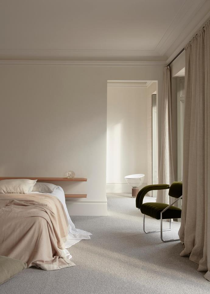Polished plaster walls create a soft glow in the master bedroom and illuminate a Flos 'Taccia' floor lamp from Euroluce. Bedding from Abode Living. ClassiCon 'Non Conformist' chair by Eileen Gray from Anibou. Carpet from Whitecliffe Imports.