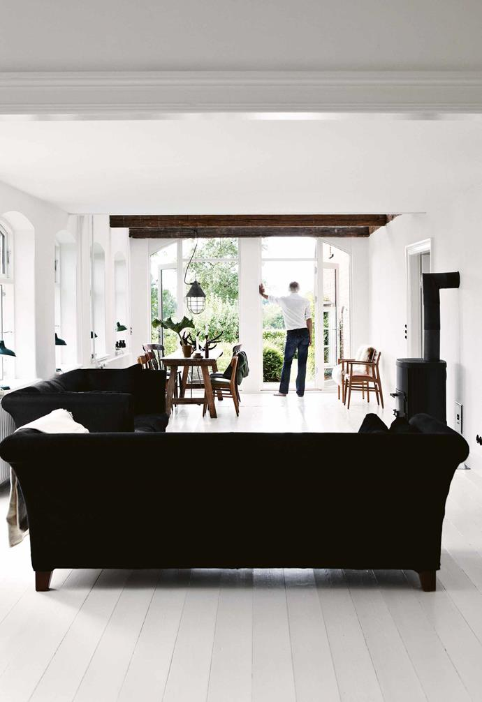 "In their quest for light and space, Bente and Lutz painted the walls, floor and ceilings white, leaving [exposed timber beams](https://www.homestolove.com.au/exposed-ceiling-beams-17206|target=""_blank"") to add a visual framework and rustic character. The expansive feel of the area is enhanced by a glass wall at the end of the living and dining zones looking out to the garden, also visible through a row of tall windows, deliberately left uncovered. <br><br>**Tip**: Ground an [all-white room](https://www.homestolove.com.au/all-white-interior-design-trend-19968