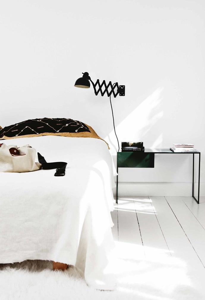 "In keeping with the home's [minimalist look](https://www.homestolove.com.au/minimalist-homes-6769|target=""_blank""), the master bedroom is simply furnished with a bed, bedside tables and wall lights. The tables were designed by Lutz and created by a local craftsman. Extra layers make the space inviting, with a shaggy rug and downy quilt contrasting with embroidered pillows. The bed is positioned to have a view straight through the living area to the wall of windows and the garden outside. <br><br>**Tip**: Bring extra comfort into a white space by adding texture. A soft rug will warm your toes on cold mornings."