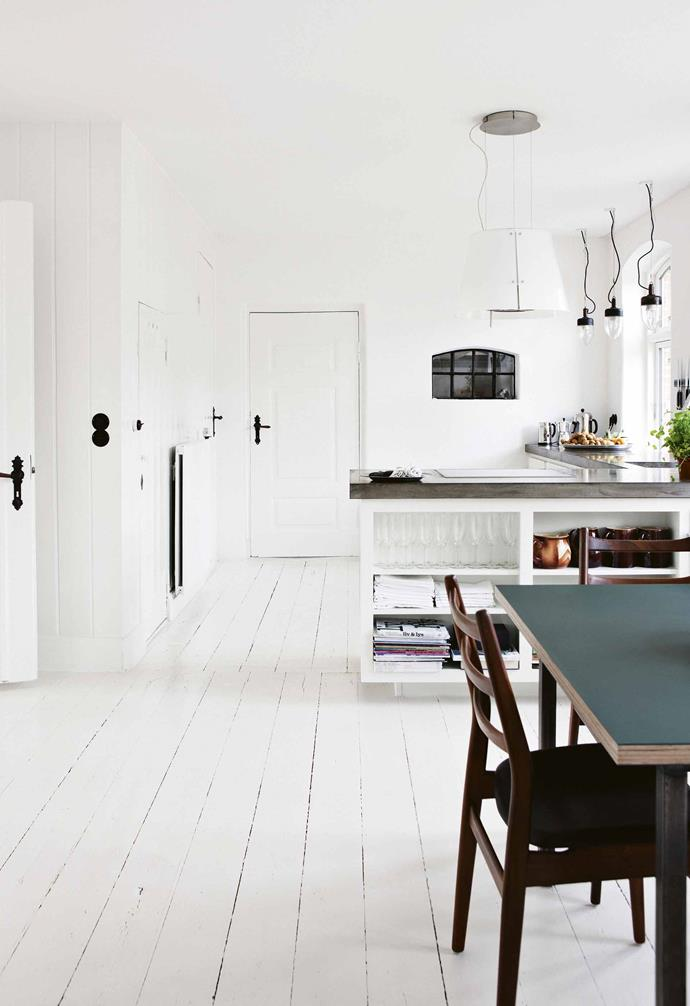 "Bente and Lutz's kitchen blends some of the home's original features, including tall cabinets, which were given a coat of [glossy white paint](https://www.homestolove.com.au/how-to-pick-the-right-white-paint-for-your-home-3741|target=""_blank"") with modern touches including a [raw polished concrete](https://www.homestolove.com.au/concrete-design-ideas-20850