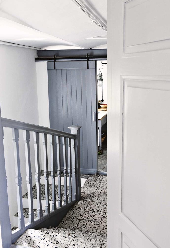 "**Bright idea** Stairs lead from the kitchen down to a utility room. The grey painted woodwork complements the original tiled floors. The statement [sliding barn door](https://www.homestolove.com.au/barn-door-17386|target=""_blank"") adds a beautiful design feature to the space."