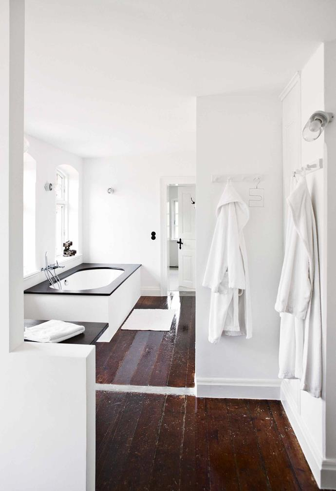 "If space is a luxury, then this bathroom has it in spades. Configured in an area that was formerly three rooms, this wet zone includes a [built-in bath](https://www.homestolove.com.au/inset-bathtubs-19355|target=""_blank"") and separate shower niche. Decoratively, Bente and Lutz wanted  to continue the slightly industrial feel of the rest of the house, so they retained the original floorboards with all their lived-in imperfections. <br><br>**Tip**: Consider leaving parts of a large bathroom untiled to make it feel more like a living zone. You'll need good ventilation to avoid too much condensation."