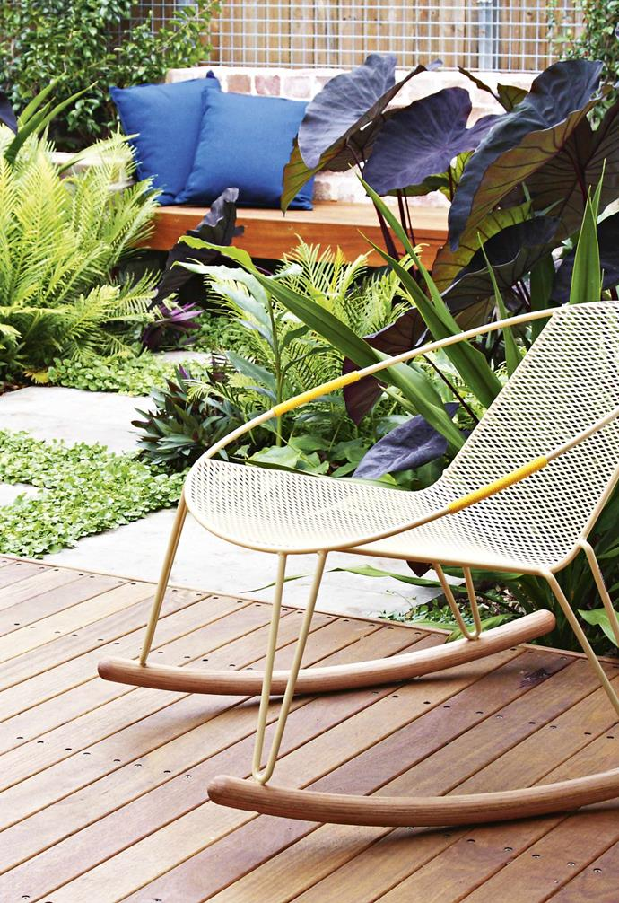 """Beside the deck and visible from the kitchen are layers of lush leafy plants with a sitting nook nestled amongst them. [Feature walls](https://www.homestolove.com.au/pros-and-cons-of-a-feature-wall-14390 target=""""_blank"""") of recycled brick surround it all, tiered to create [raised planters](https://www.homestolove.com.au/raised-garden-beds-9873 target=""""_blank"""") for even more leafy plants, while dealing with different ground levels. It's a relaxing garden that has transformed the house in terms of entertaining space. """"We were confined to the inside, but we can now have people over and sit outside,"""" says Kate. The deck is ideal for casual entertaining, offering a versatile space for a choice of tables and chairs."""
