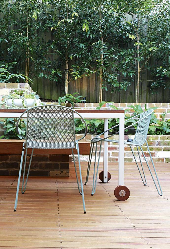 """Julia's plant choices temper the wood and brickwork, which might otherwise look harsh. The [tropical-style foliage](https://www.homestolove.com.au/tropical-plants-for-australian-gardens-19309 target=""""_blank"""") has an overall softening effect, and the vivid greens and purples enliven the area. The mostly evergreen leaves are soft to touch, their shapes and sizes creating a magical textured effect.<br><br>**Outdoor dining** Slimline [outdoor furniture](https://www.homestolove.com.au/outdoor-furniture-ideas-18385 target=""""_blank"""") ensures a light footprint in the limited space. Tiered [garden beds](https://www.homestolove.com.au/raised-garden-beds-9873 target=""""_blank"""") create depth and allow for even more greenery around the fenceline, while preventing the space from feeling hemmed in. The retaining wall and bench can act as extra seating when entertaining."""