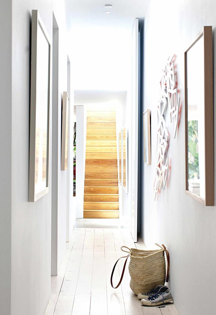 **Hallway** Whether it's to make a poky space seem larger, or to enhance the amount of light in a room, a splash of white paint always does the trick. In this hallway, white works its magic by showcasing the artwork, the lines of the floorboards and the honey-oak tones of the staircase beyond.