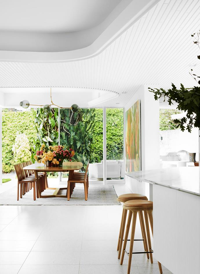 "With a mostly all-white palette running throughout this [revamped mid-century abode](https://www.homestolove.com.au/sensitively-revamped-mid-century-house-20728|target=""_blank""), pops of colour are added through timber furniture and lush greenery."