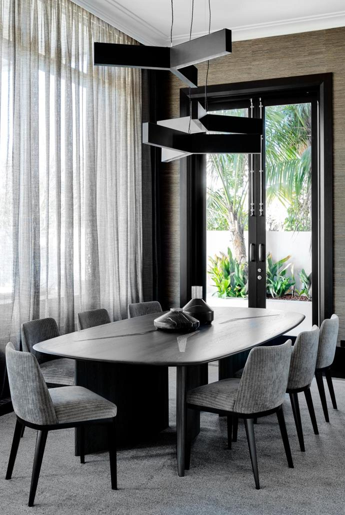 The 'Boomerang' dining table by Christian sits below a cluster 