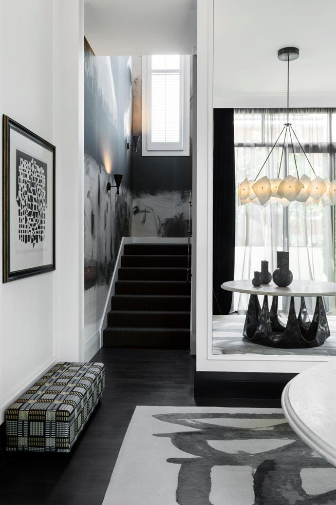 Victor Vasarely artwork hangs above a Romeo ottoman upholstered in a Dedar woven fabric. Faye Toogood designed the linen wallpaper mural, handmade in New York, going up the wall of the staircase, which sports a bespoke forged steel handrail designed by Christian and made by a local metal artist. Tom Dixon 'Beat' wall lights from Editeur line the stairwell.