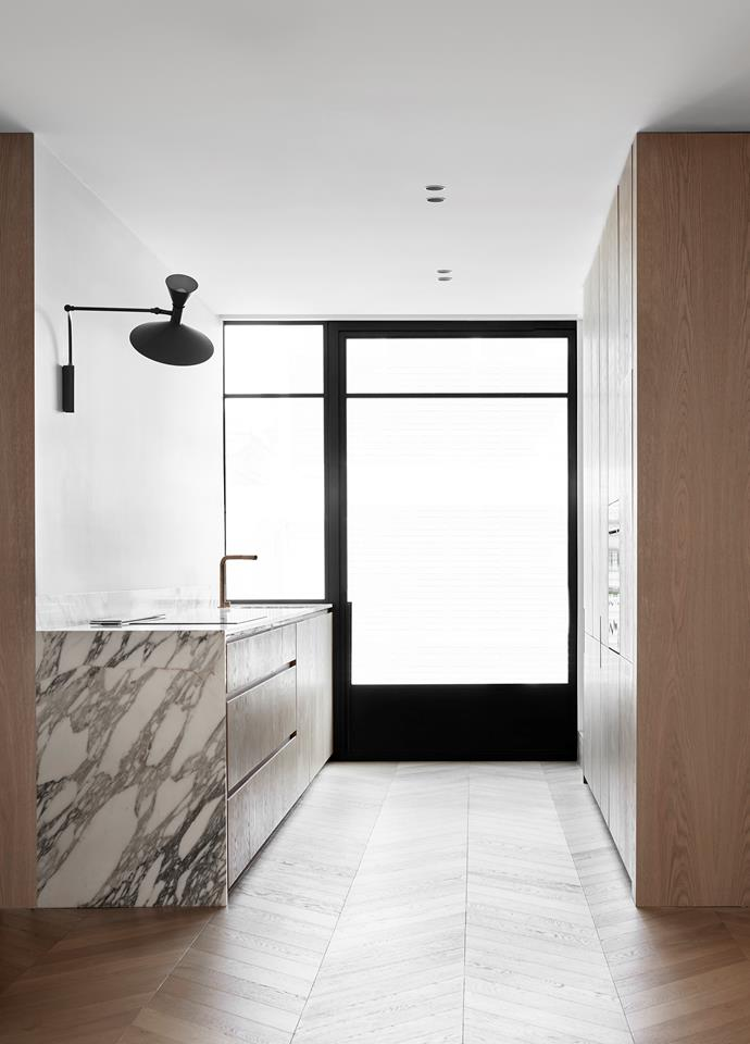 "The minimalist ambience conceived by Travis Walton thoroughly updates this galley-style kitchen in a Victorian terrace with beautiful materials and modernist classics. ""We applied a fresh approach to this refurbishment to maximise space and create an understated luxury. Minimalist detailing gives greater breathing space, mediating the character of the old with the restraint of the new."""