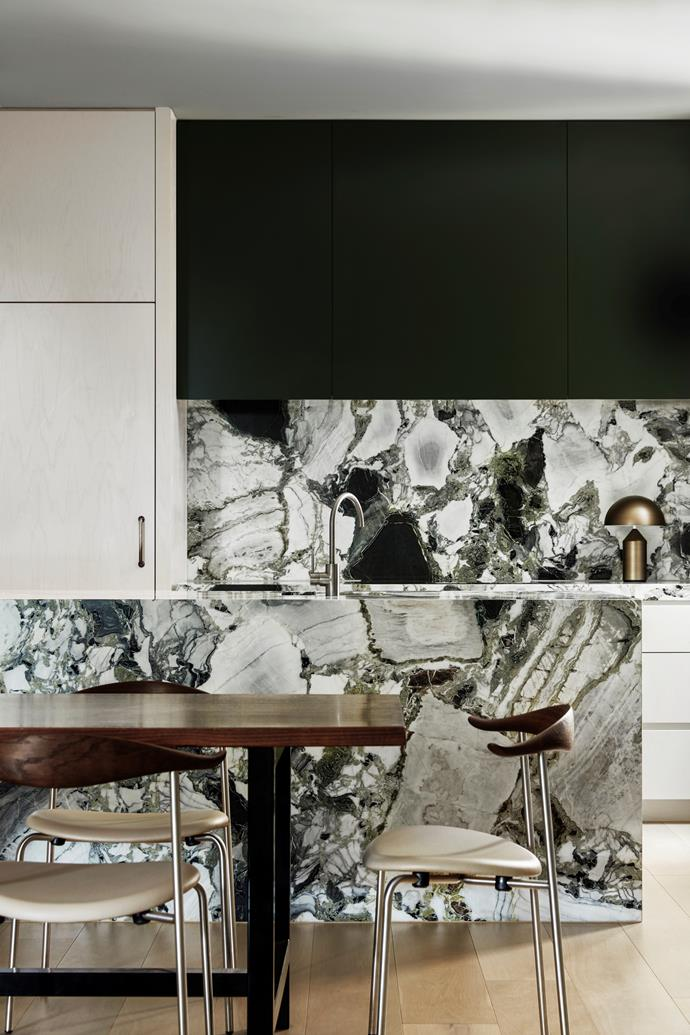 "Designer Fiona Lynch embraced a tonal palette in this [oasis-like apartment](https://www.homestolove.com.au/luxurious-yet-relaxed-apartment-in-st-kilda-21728|target=""_blank"") that was inspired by the silvered green hues of the landscape. Ice green-figured marble from Signorino gives presence to the kitchen island, holding the room like an abstract artwork. Balanced with the luxurious restraint of finishes, including polished plaster and walnut, the interior is an understated composition of subtle, tactile surfaces."