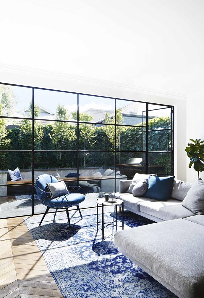 """Ceiling to floor steel-framed windows connect the living room with the courtyard in this [revamped Edwardian home](https://www.homestolove.com.au/modern-edwardian-semi-renovation-18524