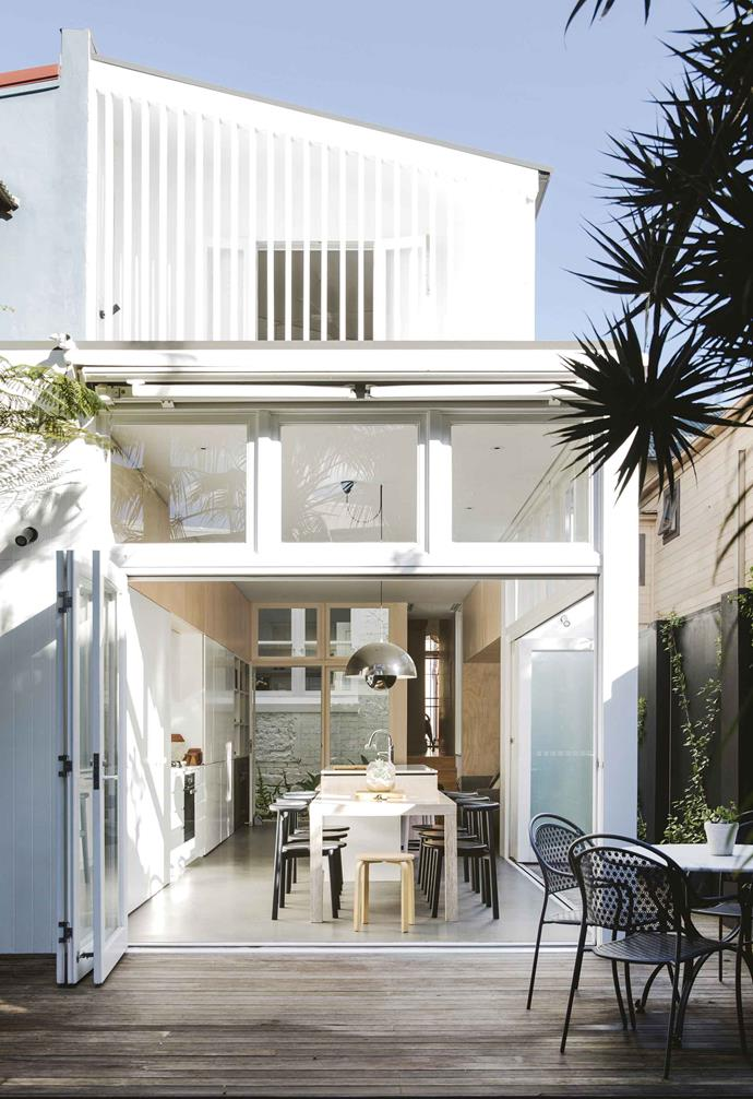 """Striking white-framed bi-fold doors extend the open-plan kitchen and living space to include the deck in this [relaxed terrace Paddington](https://www.homestolove.com.au/relaxed-terrace-paddington-18366
