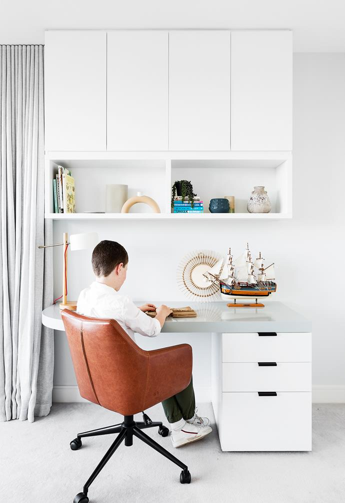"Set on the top floor, the [children's bedrooms](https://www.homestolove.com.au/modern-childrens-bedroom-ideas-13322|target=""_blank"") were greatly expanded, giving each one their own ensuite and custom joinery. The renovation also unexpectedly gave son Jack, pictured above left, the best view in the house. ""People always ask why we didn't claim Jack's room for ourselves, but I'm really happy with the layout - it works well to have all the kids together,"" says MJ. Designed by Imogene, Jack's desktop, in Grey Pail by Dulux, has the same curved motif that's repeated throughout the home. MJ and Viv opted for the leather desk chair from Freedom because it added a more masculine texture to the room. ""Jack loves it, mainly because it swivels,"" explains his mother, with a smile."