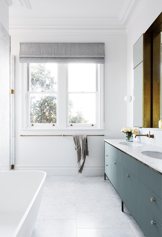"The bespoke vanity unit, designed by Imogene and then made by Elan, features similarly ribbed panelling to the kitchen bench. Viv suggested the panelling be painted in the soft tones of Dulux Pozieres. ""All-white bathrooms can sometimes feel clinical, so we added interest with the warm green accent,"" says Viv. ""The subtlety of the green works beautifully with the marble and brass."""