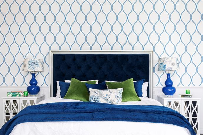 """Navy blue and olive green are a regal combination in the couple's bedroom on the upper level. The bed, featuring a velvet headboard, was custom-made through Domayne, with the royal blue tones echoed in an Adairs throw and custom cushions. As in all the bedrooms, wallpaper forms a decorative backdrop, with a 'Camber' Thibaut design chosen as the focal point above a dado rail. """"I've always loved blue and it works so perfectly with the Hamptons style,"""" reflects Mieke about her home's signature colour. For a cohesive feel, floral Westbury 'Longwood' fabric from Canvas + Sasson used on the cushions and bedside lamps continues through to the ensuite in the feature blinds."""