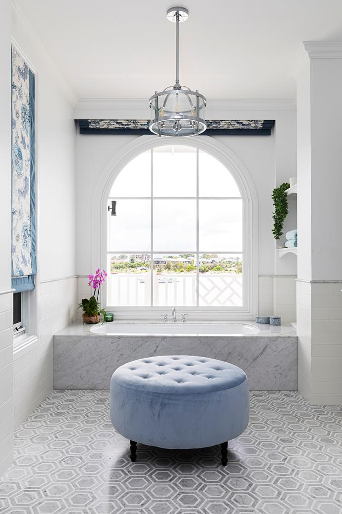 """""""I saw a photo on Pinterest years ago of a bath below an arch window and knew it was what I wanted to create in the ensuite, and it worked out perfectly,"""" enthuses Mieke. Bathed in beautiful natural light, the Reece Roca undermount bath, surrounded by Carrara marble sourced from GMG Stone, complements the soft grey and white Carrara hexagonal floor tiles from Tile & Stone Gallery. Soft furnishings, including a duck egg blue ottoman by Custom Cushions by Kylie, and automated blinds, also enhance the sense of luxury. A Vermont 4 light pendant from The Lighting Superstore adds after-dark ambience."""