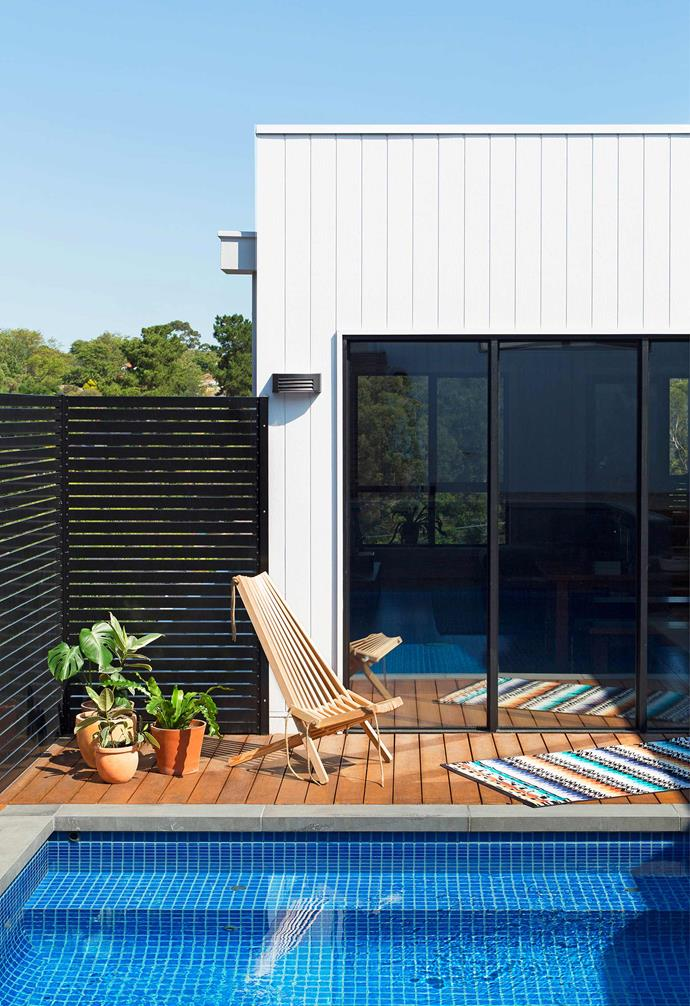 """Ceramic mosaic tiles add a striking visual feature to the pool of this [split level house built on an awkward sloping site](https://www.homestolove.com.au/a-split-level-house-design-for-an-awkward-sloping-block-5141