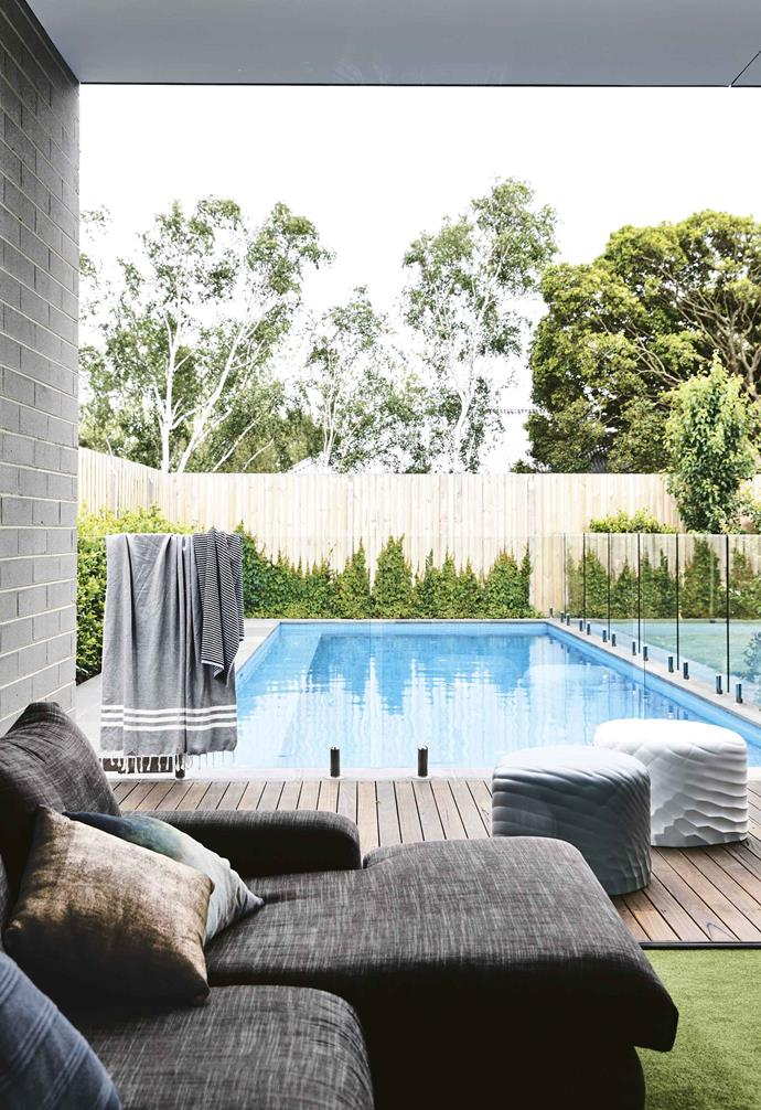 """Glass pool fencing allows clear sightlines from inside this [contemporary family home](https://www.homestolove.com.au/timber-brick-house-melbourne-17933
