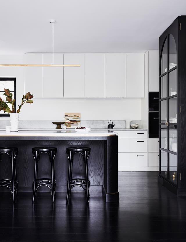 """This monochrome kitchen's curved island bench is one of many elements in this [elegant home](https://www.homestolove.com.au/modern-art-deco-home-20290