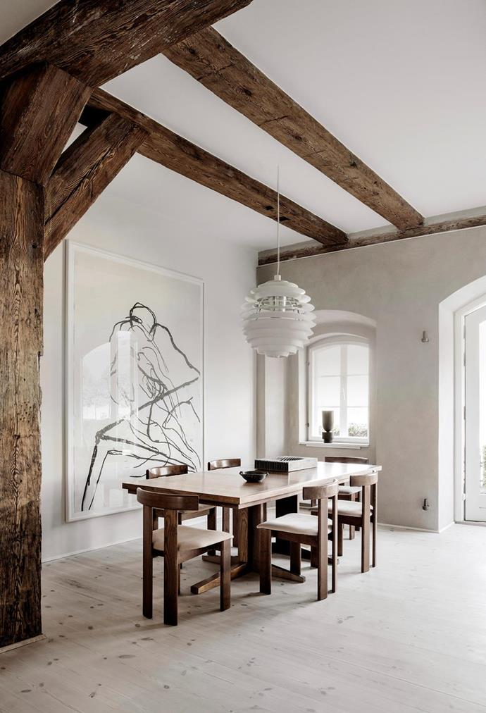 "Curves in the chair backs, a spherical Louis Poulsen 'PH Louvre' pendant light and oversized artwork by German artist Paco Knöller soften the minimal dining zone in this [industrial-style apartment with exposed beams in the heart of Copenhagen.](https://www.homestolove.com.au/exposed-timber-beams-20584|target=""_blank"")"