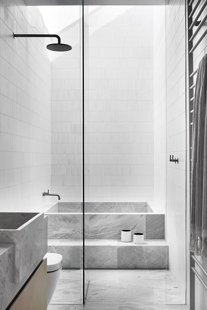 """We wanted to create a pared back, low maintenance and restorative sanctuary,"""" says architect Kathryn Robson. """"It was important that it have a sense of luxury and escape."""" The centrepiece of this bathroom is its generous inset bath, formed from stone slabs."""