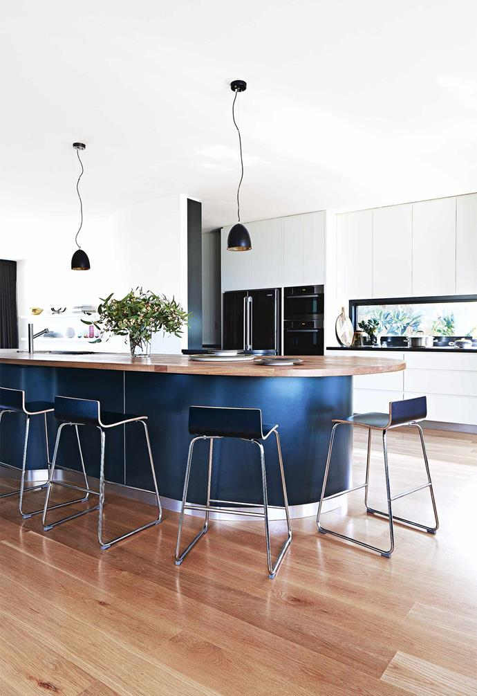 "Incorporating a central lap pool and a curved rammed earth wall, there's a certain sophisticated edge to the seaside sanctuary. We get the inside scoop...<br><br>**Kitchen** European oak features on the [island benchtop](https://www.homestolove.com.au/kitchen-inspiration-13-of-the-best-island-benches-17943|target=""_blank""), as well as on the floor. The black facade and stainless-steel kickboards lend a touch of luxe"