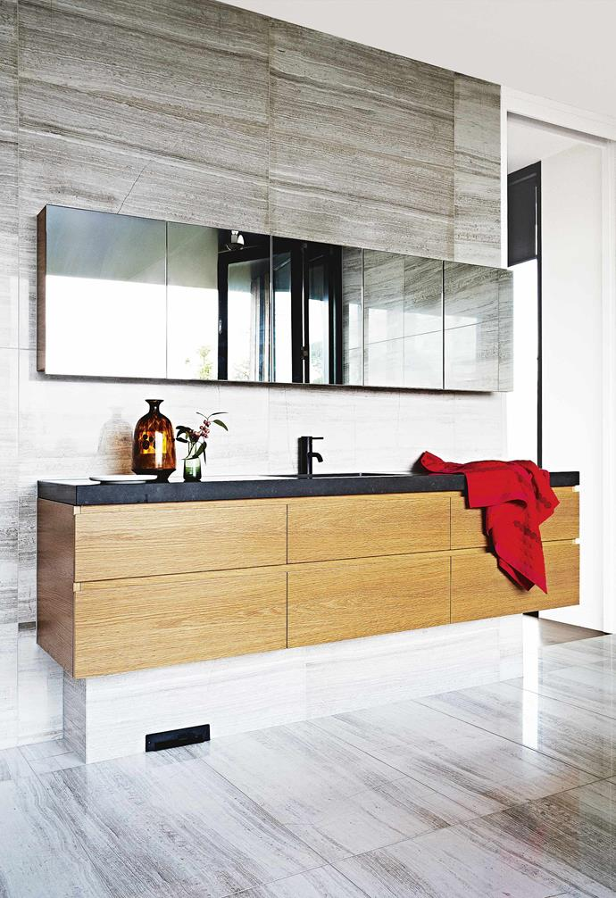 """**The curved rammed earth wall was a stroke of genius – how do you attempt to construct something that is so out of the box?** <br><br>The idea of a straight [feature wall](https://www.homestolove.com.au/pros-and-cons-of-a-feature-wall-14390 target=""""_blank"""") seemed too run of the mill, so we wanted to construct a curved wall on such a scale that it would break up the traditional straight lines of the home.<br><br>**Bathroom** Natural textures shine with limestone tiles and a European oak vanity."""