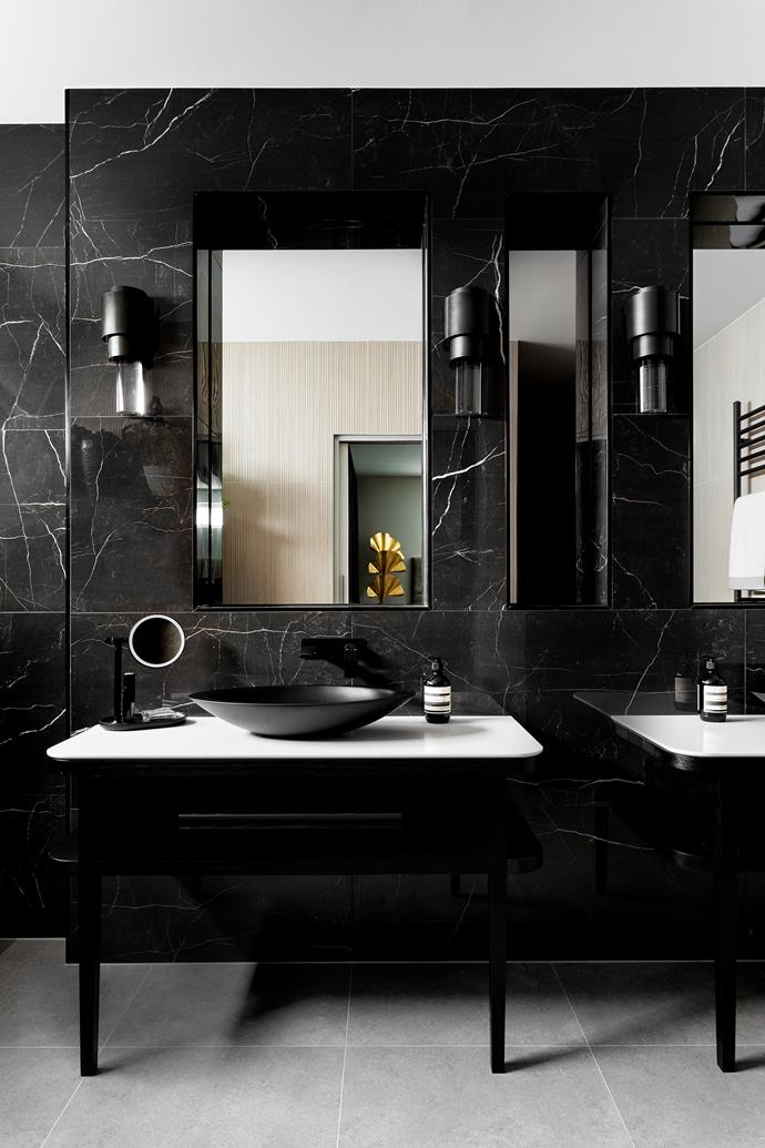 The owners of this Melbourne home love the luxuriousness of a beautifully appointed hotel bathroom and requested that interior designer Peter Schaad create that feel for their ensuite. The transformation is built upon beautiful new tiling: a natural, neutral tile for the floor, dark marble-look tiles behind the vanities and a textural corrugated tile for the other wall.