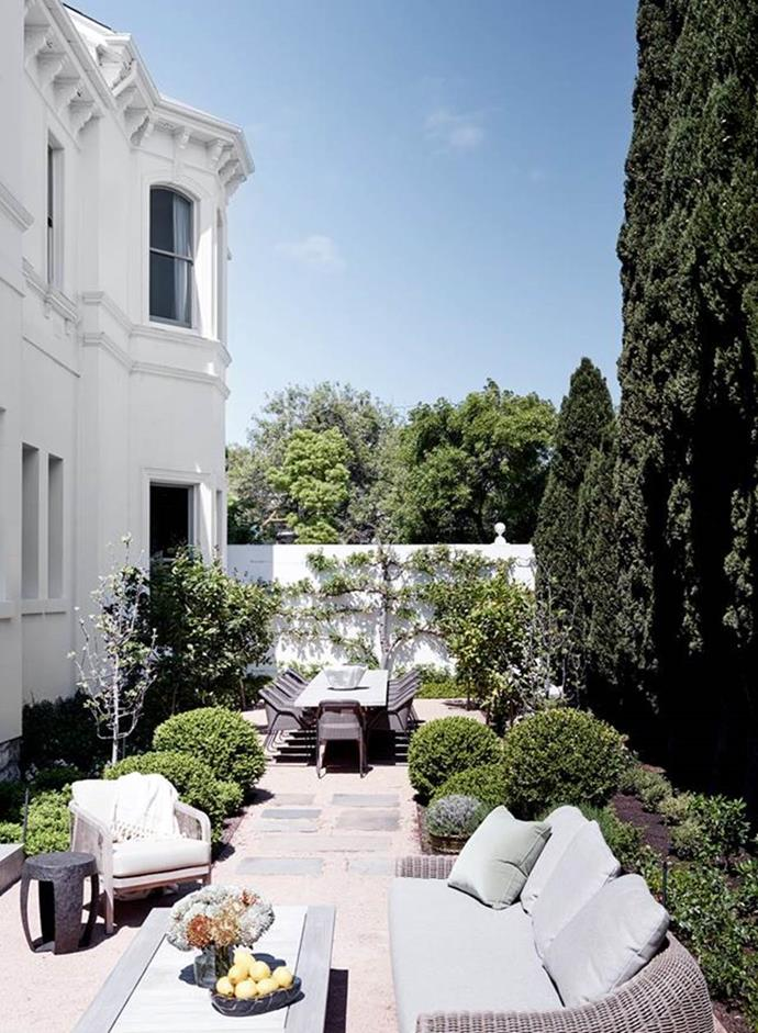 """This outdoor living space is surrounded by manicured gardens by Paul Bangay, in the courtyard area of an [Italianate mansion](https://www.homestolove.com.au/restored-italianate-mansion-toorak-21162