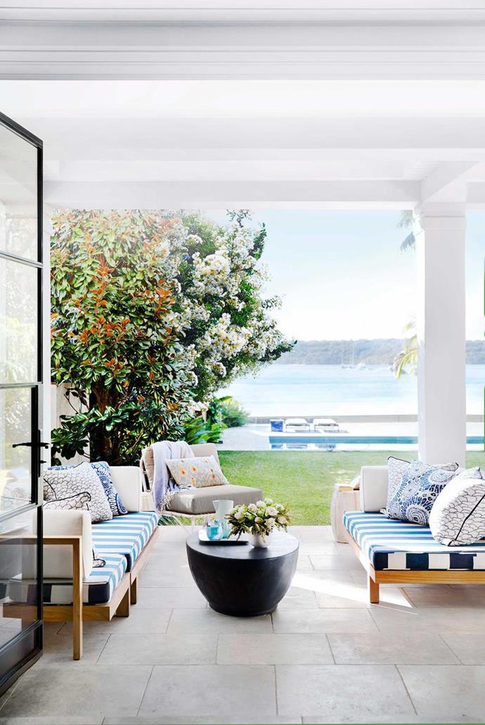 This outdoor living space features lounges covered in a combination of printed outdoor fabrics.