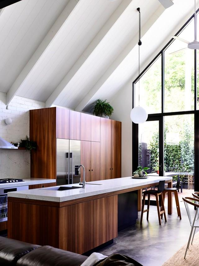 "This bright and airy [renovated Melbourne kitchen](https://www.homestolove.com.au/inner-city-renovation-advice-6704|target=""_blank"") features steep cathedral ceilings. While it may appear to be a timber kitchen, it is actually constructed from red gum wood veneer for a more durable finish. It has been paired with reconstituted stone benchtops."