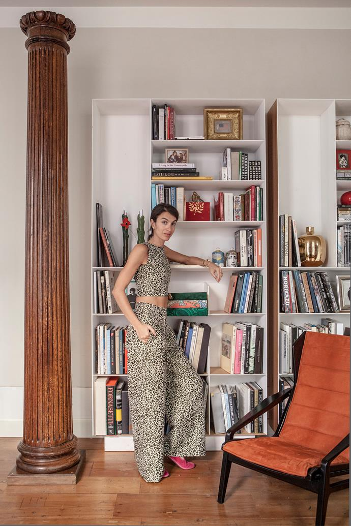 "Homeowner, designer and textile consultant Marta Ferri has worked with brands including Superga, Birkenstock, and more recently Matchesfashion and Molteni&C. She's known for designing couture garments using upholstery fabrics. Marta, pictured in front of her library of design tomes, says when decorating her home she trusted her intuition and ""everything seemed to create a great harmony and the sense of home we were looking for""."