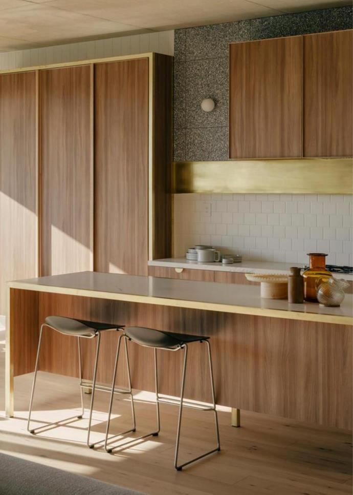 "In the kitchen of this [modernist apartment in Fitzroy](https://www.homestolove.com.au/modernist-apartment-with-timeless-appeal-21754|target=""_blank""), Melbourne, a sleek shelf and timber joinery pulls all in brass bring a gleam to the timeless neutral interiors."