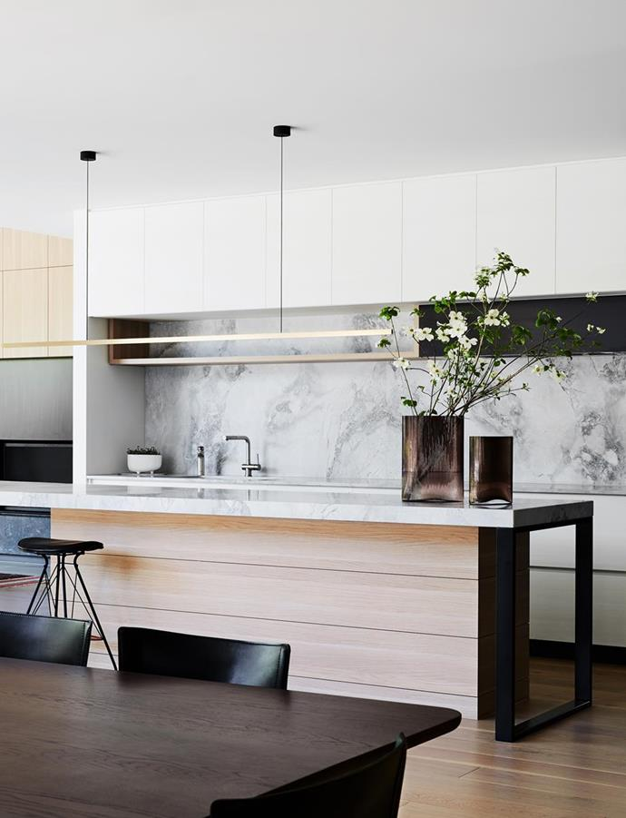 """The kitchen island bench is the showpiece of the kitchen,"" said the architect of this bold new residence in Melbourne's south east. ""The Superwhite Dolomite honed stone top is soft and inviting and looks more like a piece of furniture, with looped legs at each end, and it has seating on both sides to fit the whole family,"" around the timber panels that add linear contrast to the bench."