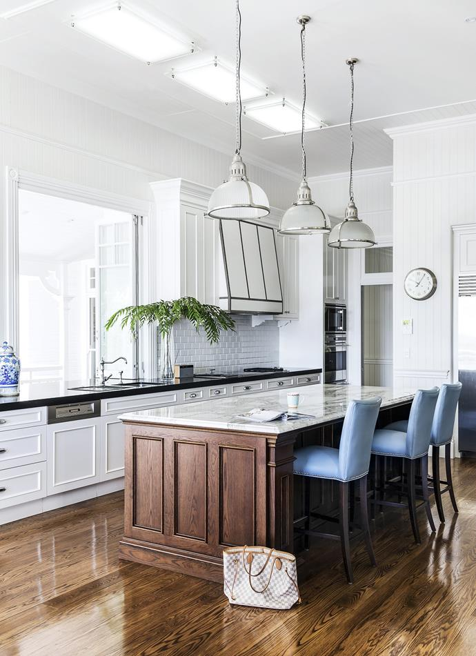 "The impeccable finishes, including elegant dark timber panelling around the island bench are what really make the kitchen in this [classic Queenslander](https://www.homestolove.com.au/classic-queenslander-updated-for-family-living-2577|target=""_blank"") shine."