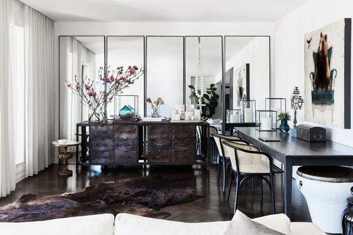 Mirrors are used to make this lower-ceilinged space feel larger. Recycled timber table bought in New Zealand and chairs from West Elm (US). Antique table and industrial console, both bought in France. Existing flooring. Painting purchased in the US