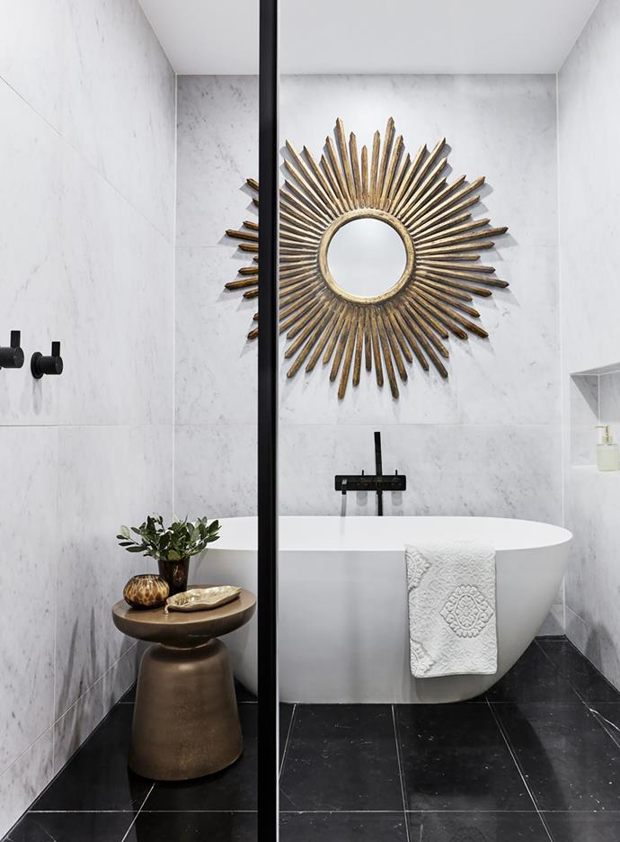 A timber-framed starburst mirror found in Indonesia is positioned over a Moda bath from ACS Designer Bathrooms.