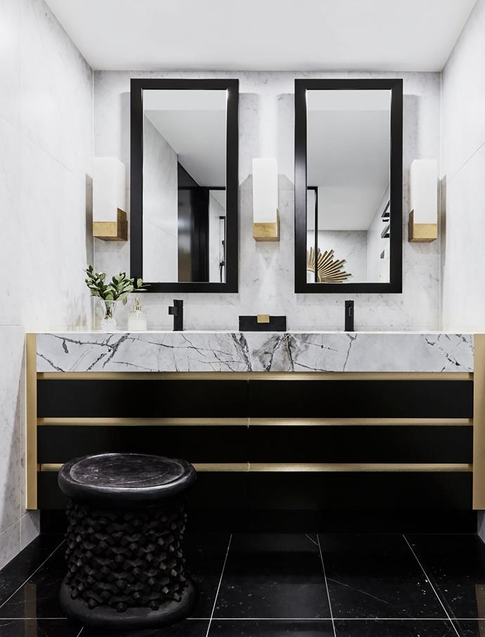 The brass-trimmed vanity is topped with Manhattan marble from Gitani Stone and taps by Sussex. Covet Tall Box alabaster and brass wall sconces by Kelly Wearstler.
