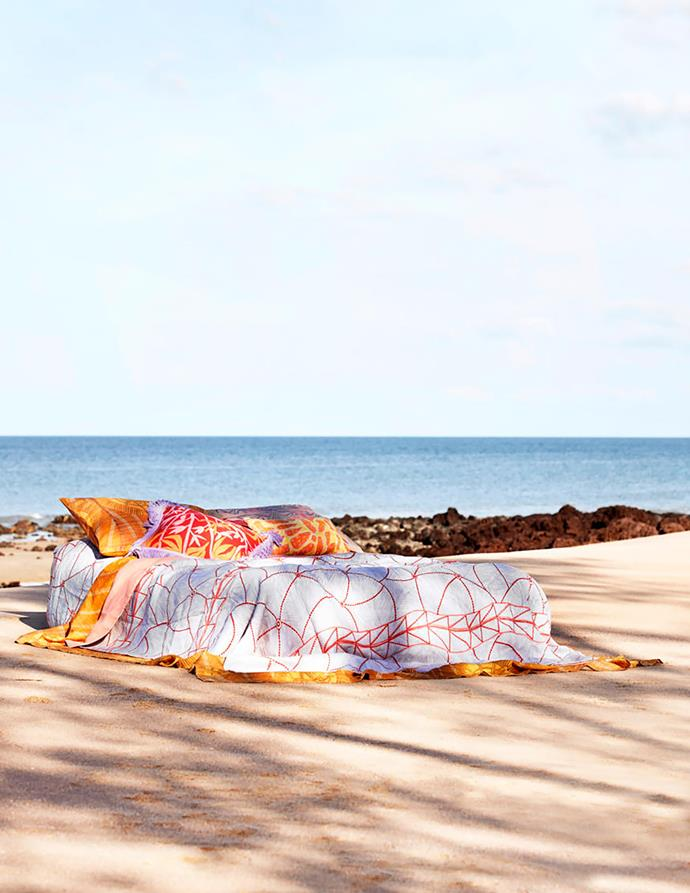 The elegant Kunkurra linen quilt cover, designed by Janet Marawarr, features swirling blue lines with a delicate web-like pattern in deep shell pink. It depicts the kunkurra, a spiralling wind common during the wet season in Arnhem Land, and relates specifically to several sites important to Janet's husband's clan. The cushions are a combination of the Marebu, Manwak and Ngarduk Kunred designs.