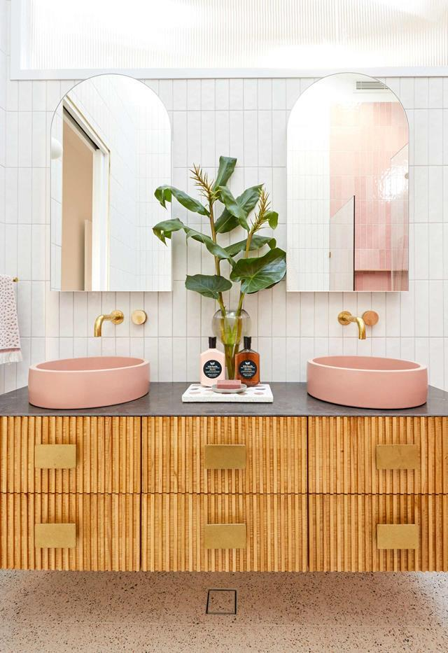 A fluted glass window allows light to flood into this Palm Springs-style bathroom created by Jimmy and Tam from The Block 2020. The pink tiles were matched with pink concrete circular basins, a floating timber vanity and terrazzo tiles on the floor.