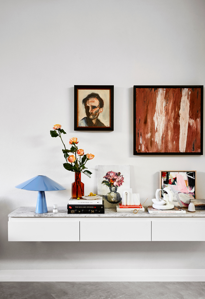 "[Floating joinery](https://www.homestolove.com.au/custom-joinery-ideas-18234|target=""_blank"") with a limestone top displays the family's collection of books, art, music and accessories. On the wall are two artworks by Steve Salo, Head of Duchamp and Roses in Jade Coloured Vase on the left and Paige Northwood's Company and Antonia Mrljak's It Comes Before Everything on the right."