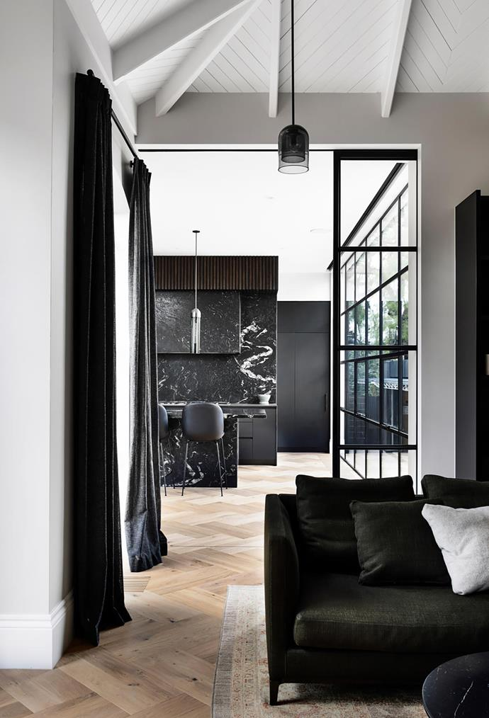 Dark-grey drapes and furniture in the informal living area provide a strong accent against the pale oak floors. Minotti 'Andersen' sofa from De De Ce. Articolo 'Lumi' pendant light.