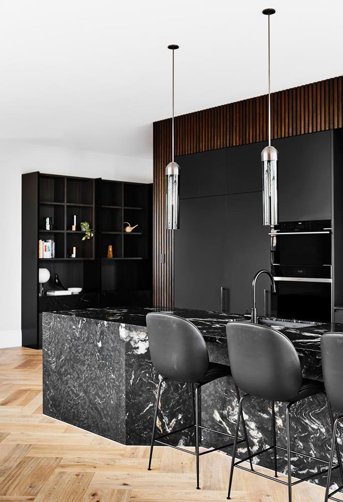 The dark and moody kitchen features a black granite island bench framed by black laminate joinery. Gubi 'Beetle' bar stool from Cult. Articolo 'Float' pendant lights. Wolf Contemporary oven and steam oven. Sub-Zero integrated refrigerator. Brodware Yokato kitchen mixer with pull-out spray.