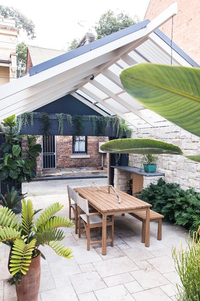 """A pergola with a transparent polycarbonate roof provides protection from the elements and imbues the space with a conservatory feel in this [outdoor area](https://www.homestolove.com.au/25-small-garden-design-ideas-6659