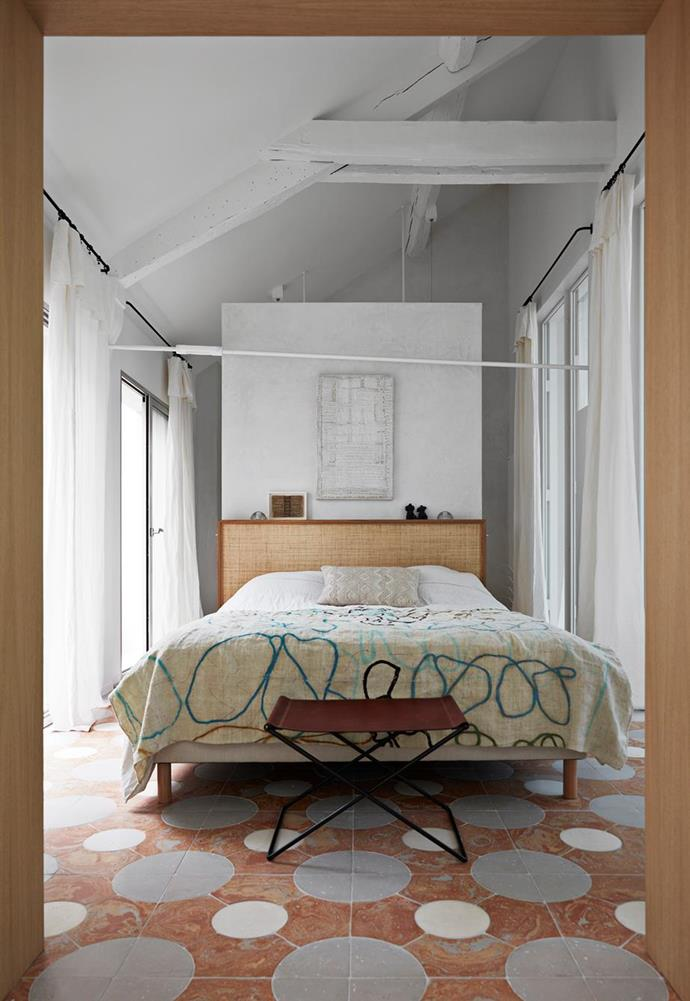 """The master bedroom features a custom-made bed, luxe linens and an artwork by Nadine Altmeyer that hangs above the bed on the partition to the adjoining ensuite in this [French gallerist's Parisian apartment](https://www.homestolove.com.au/french-gallerist-home-paris-21799