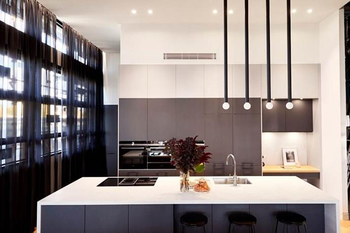 Bianca and Carla's sleek kitchen with statement pendant lights.