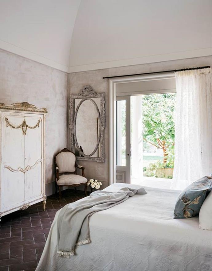"""A guestroom that looks like a European holiday. With a French antique armoire and wall mirror brought back from the UK, this rustic room looks like it's been here forever. The white curtain, linens and neutral tones give an early feel to this otherwise glamorous, [beach villa in Palm Beach](https://www.homestolove.com.au/palm-beach-villa-19320
