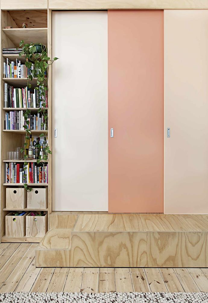 """**Pretty in pink** A set of sliding doors neatly screens off the master bedroom when needed; when left open though, the sense of space in the apartment increases. """"After it was decided to paint the doors in three shades, the choice of colour came about quite organically,"""" says Clare. """"The peach and salmon colours really complement the plywood."""" <br><br>**Tip**: Give an entry impact with a bold makeover using tones in the same colour family."""
