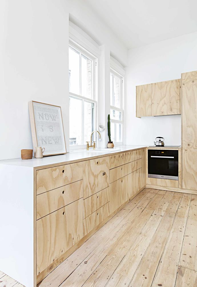 **Pared back** A simple palette of stark white and pale timber helps to accentuate a sense of space within the home, while generous windows allow ample natural light to enter. Circular hollowed pulls in the kitchen cabinetry ensure a streamlined look within the space. <br><br>**Tip**: The timber and white palette helps to maximise natural light and a sense of space.